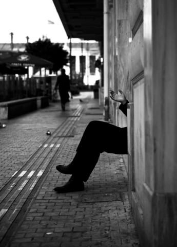 A man smoking outside of a building - fotokunst von Nasos Zovoilis