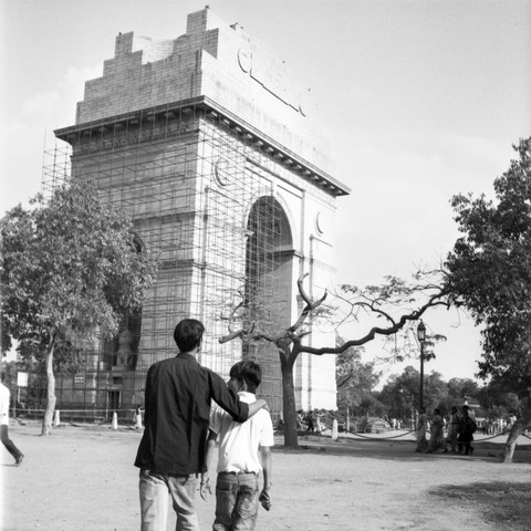 Zwei Jungs gehen vor dem India Gate in Neu Delhi spazieren.  - fotokunst von Shantala Fels