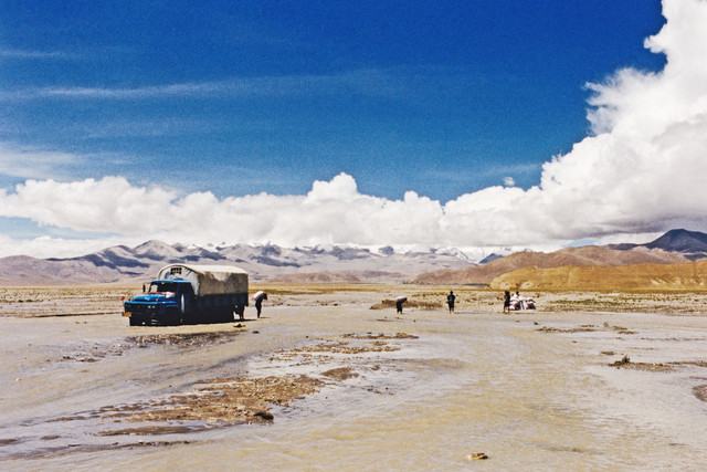 A lorry stuck in a river, Tibet, 2002 - Fineart photography by Eva Stadler