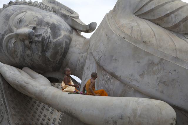 Monks sitting on big Buddha statue, Laos - Fineart photography by Christina Feldt