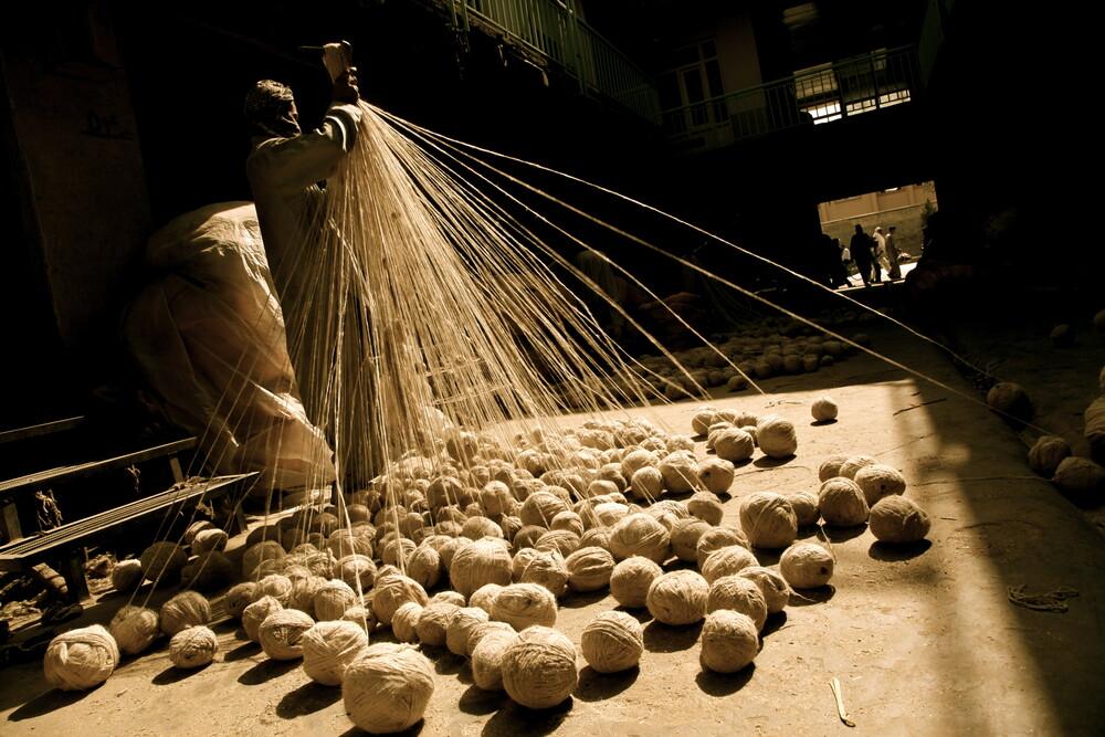 A man is making skein of wool fibers in a local market  - fotokunst von Rada Akbar