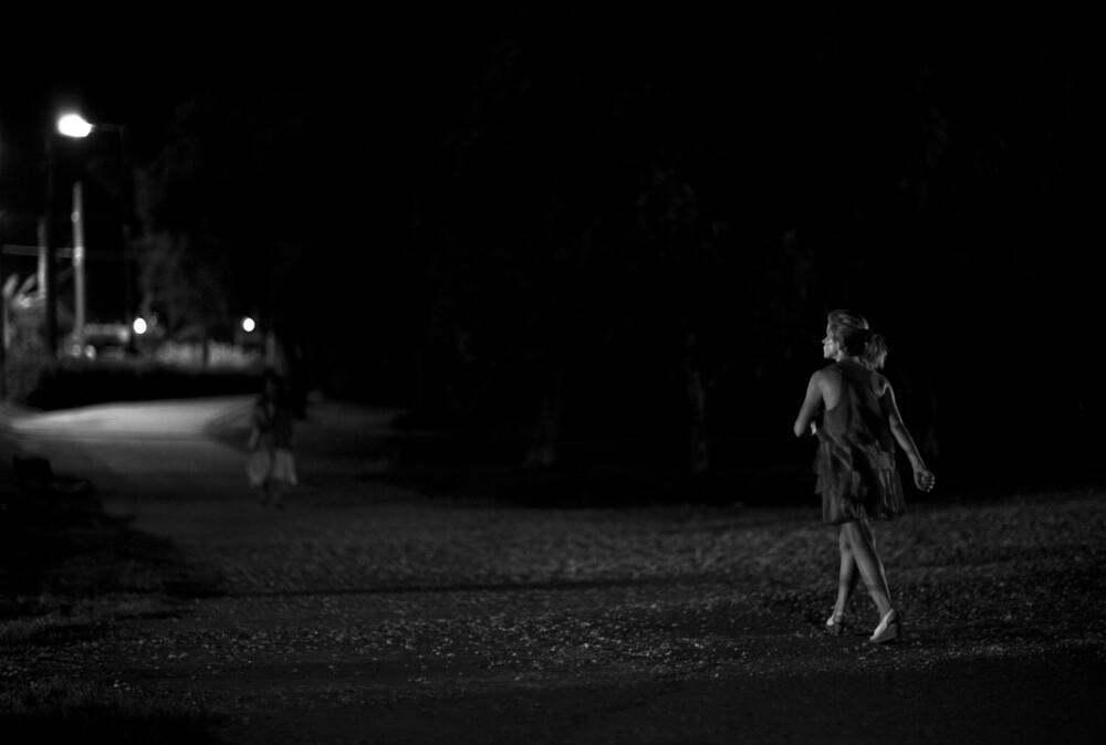A woman walking in the dark - fotokunst von Nasos Zovoilis