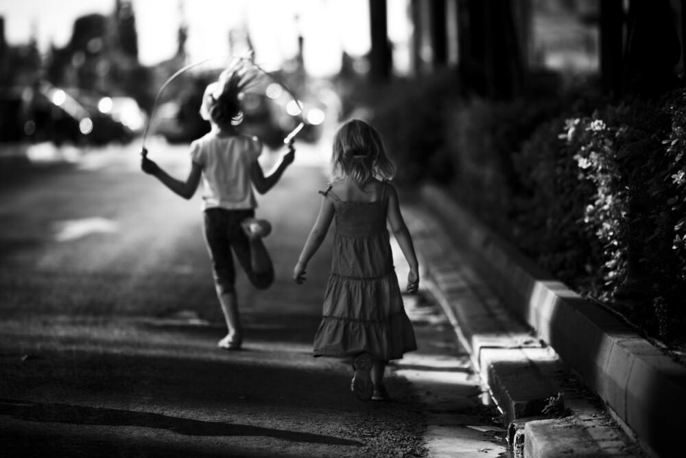 Two girls playing on the street - fotokunst von Nasos Zovoilis