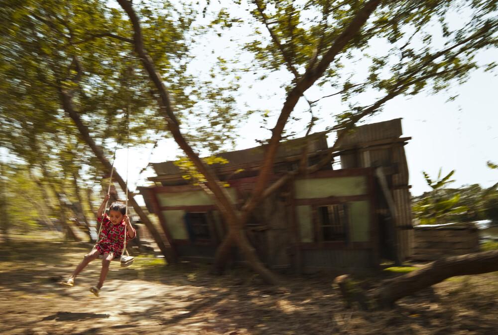 Boy playing on a swing, Bangladesh - fotokunst von Jakob Berr
