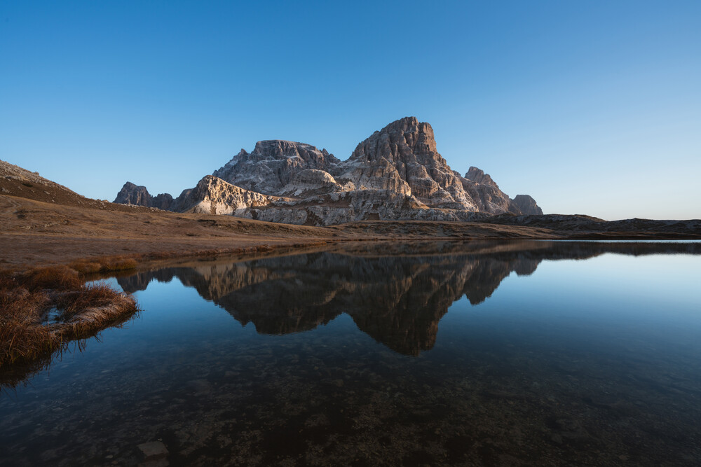 Mountains reflected in a lake at Tre Cime di Lavaredo - fotokunst von Simon Migaj