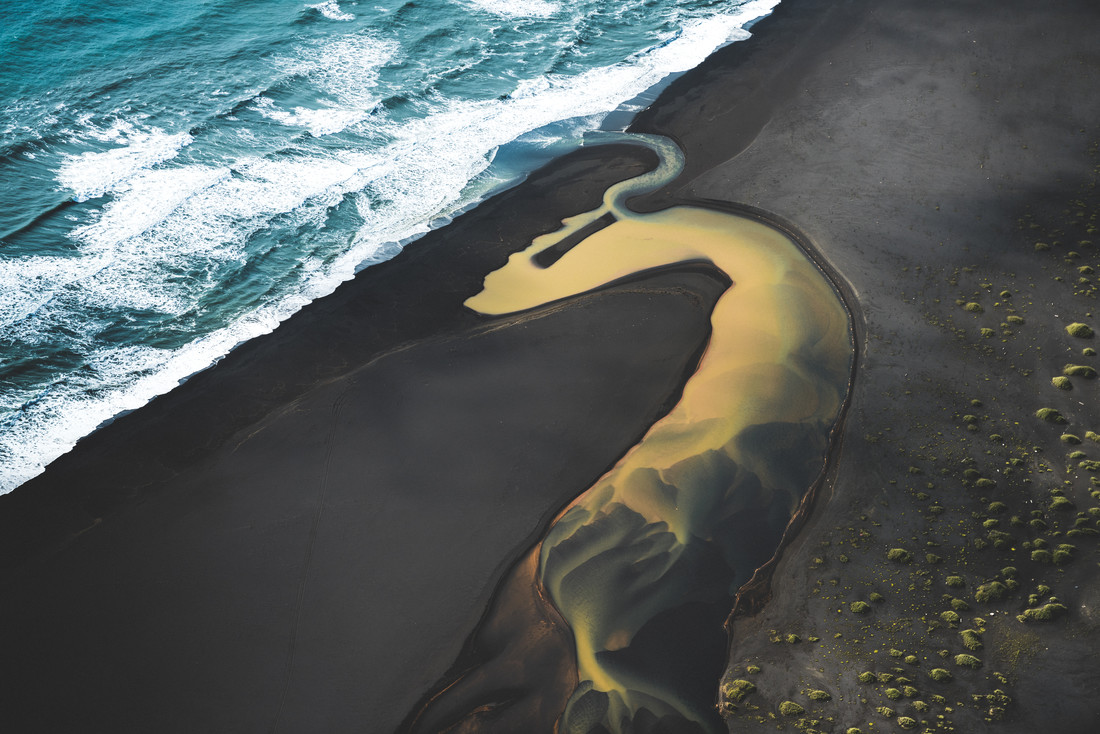 Colored river heading into the ocean in Iceland - Fineart photography by Roman Königshofer