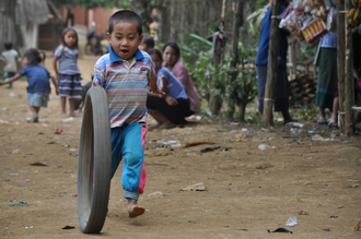 Thomas Heinrich, Boy playing with a tire (Laos, Asia)