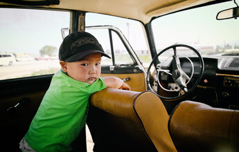 Boy in old Lada in Kyrgyzstan - Fineart photography by Victoria Knobloch